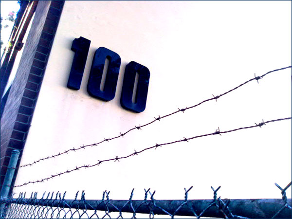 Photograph of a street number, 100, with barbed wire