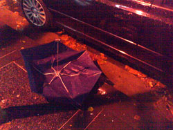 Photograph of a broken umbrella, lying next to a car on a dark street.
