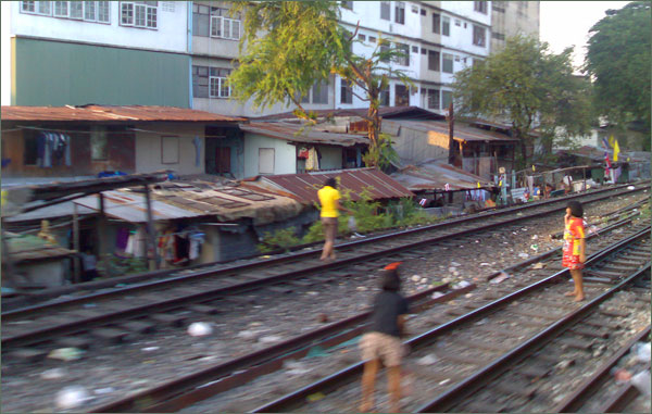 Photograph of girls playing on the railway in Bangkok, with the slum in the background