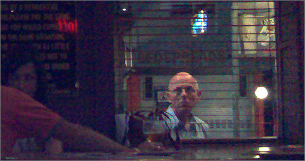 Photograph of man peering thru pub window (very indistinct)