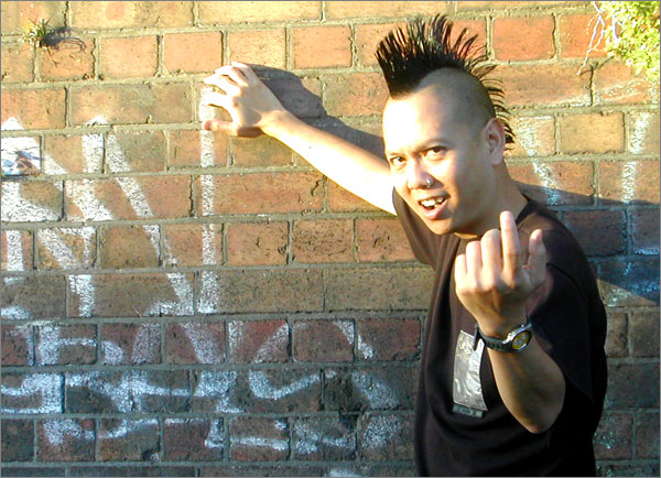 Photograph of Trinn Suwannapha with long mohawk, giving the finger