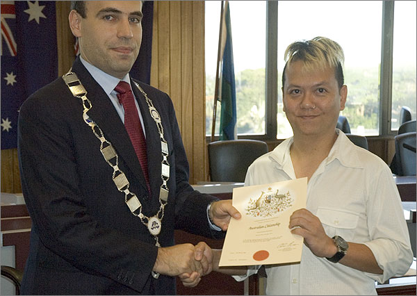 Photograph of Mayor of Marrickville, Dimitrios Thanos, with Trinn Suwannapa, holding an Australian Citizenship certificate