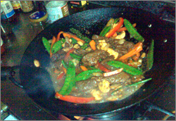 Photographs of kangaroo red curry stir-fry being prepared in a wok and served on a plate