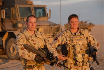 Photograph of two Ausralian soldiers in Afghanistan, standing with weapons in front of their vehicle