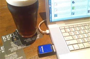 Photograph of Telstra Next G cardbus modem in my MacBook Pro, with a pint of Kilkenny nearby