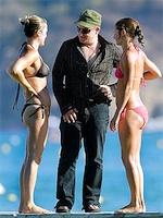 Photograph of Bono with two bikini-clad women