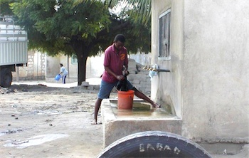 Photograph or rural Tanzanian village, with man using hand pump to get water