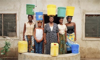 Photograph of Tanzanian women with brightly-coloured plastic water containers balanced on their heads
