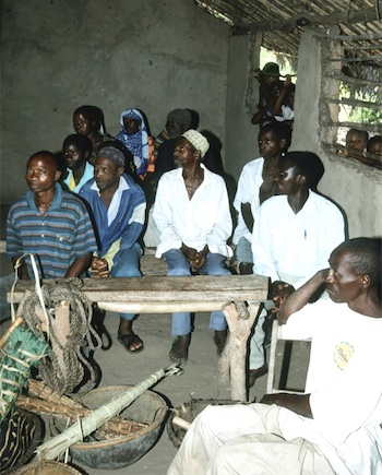 Photograph of Tanzanian villagers meeting in a hut with a rough-hewn wooden table and basic household utensils