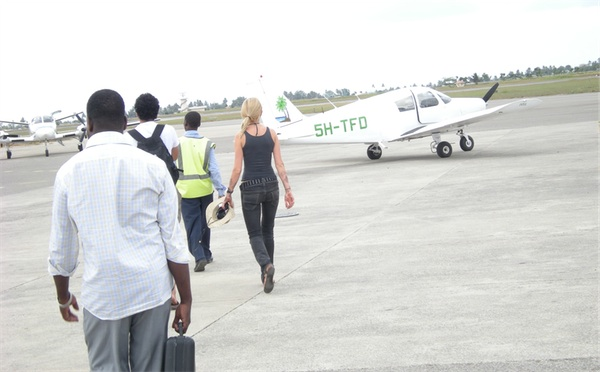 Passengers walking past a light aircraft to a ZanAir Cessna 404 Titan