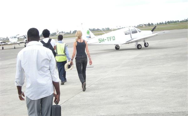 Passengers walking past a light aircraft to a ZanAir Cessna 404 Titan