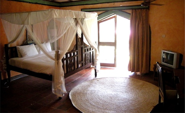 Photograph of a room at the Zanzibar Beach Resort, showing mosquito nets on the four-poster bed