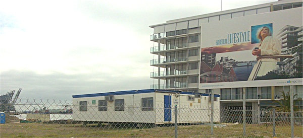 Photograph of newly-built apartment and signage reading Harbour Lifestyle