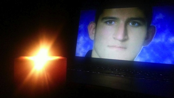 Photograph of Reza Berati on screen, with a candle in the foreground