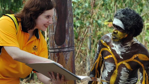 Jill Charker from the Bureau of Statistics explains a census form to traditional dancer Peter Gurruwiwi in northeast Arnhem Land