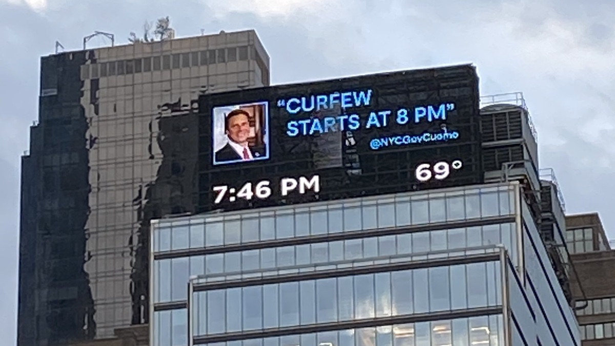 A New York cityscape with a huge TV screen showing the message: Curfew starts at 8pm @NYCGovCuomo.
